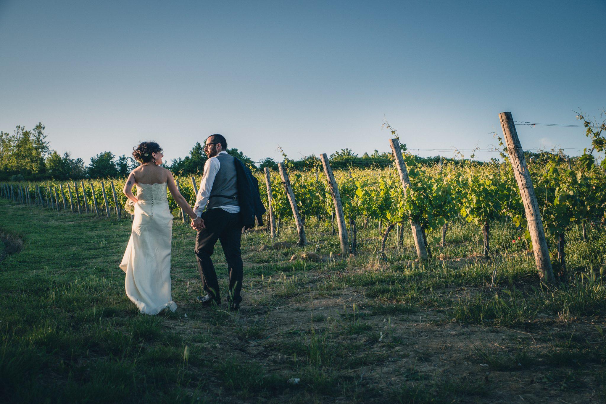 Sposi in cammino nelle vigne al tramonto