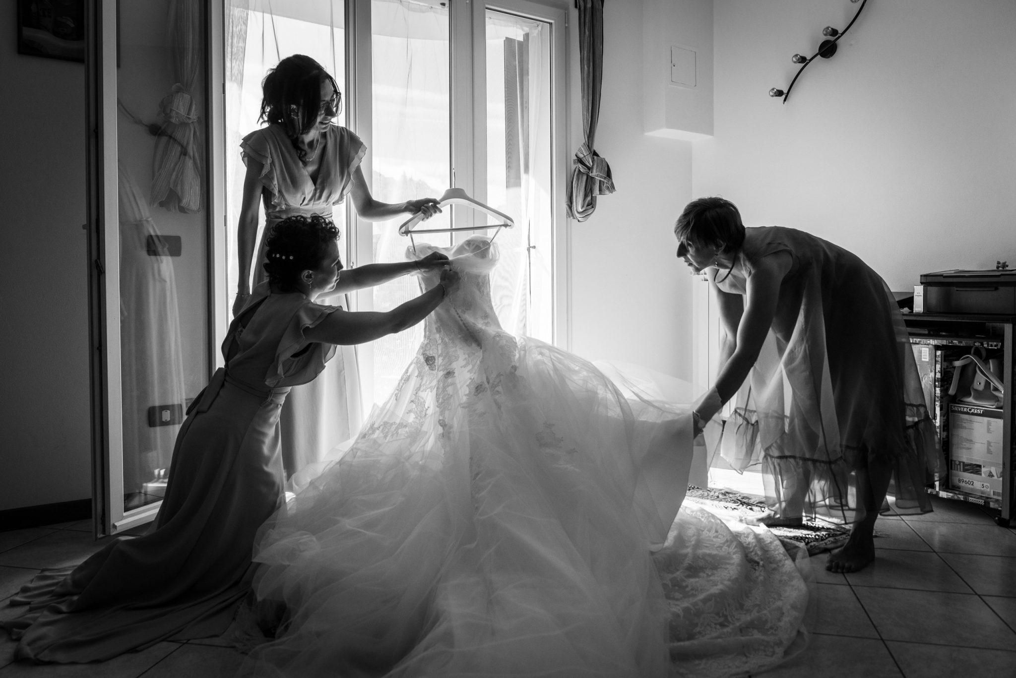 Damigelle preparano il vestito della sposa