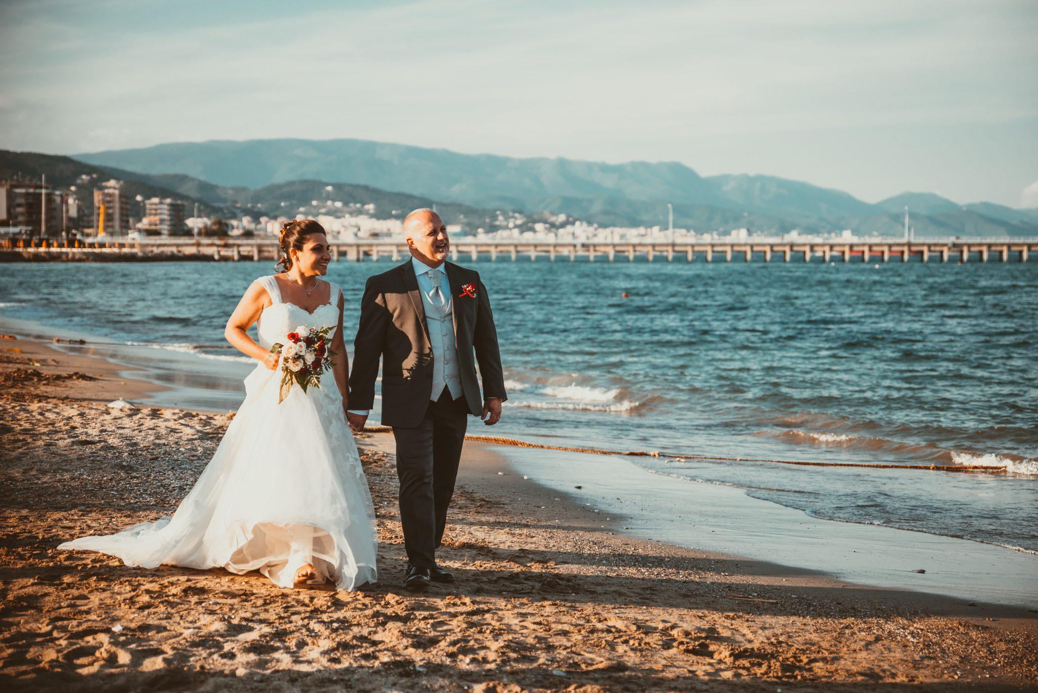 Passeggiata degli sposi in spiaggia in riva al mare