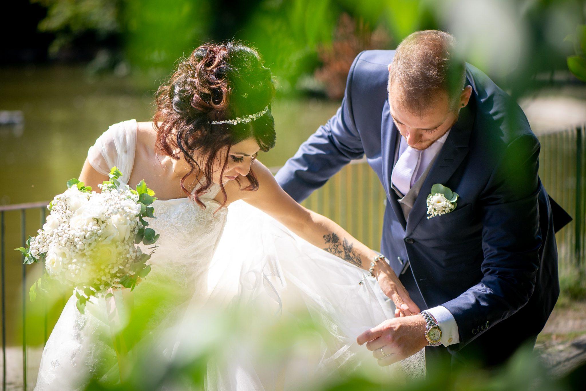 Sposo aggiusta vestito alla sposa